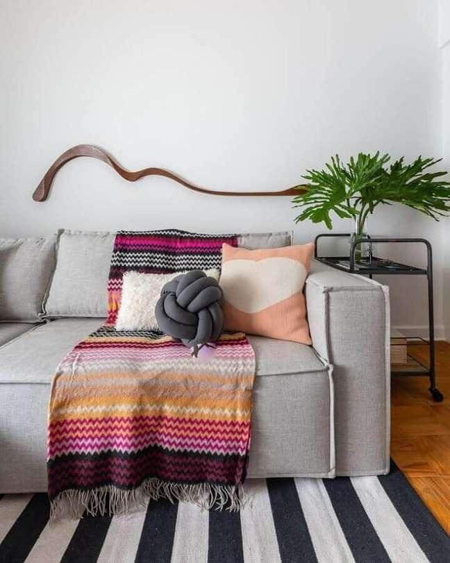 58. Sala simples decorada com manta e almofadas para sofá cinza – Foto: Gisele Rampazzo