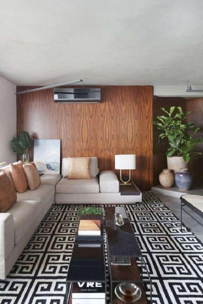 44. Parede de madeira para sala decorada com tapete geométrico e almofadas para sofá cinza claro – Foto: Casa Vogue