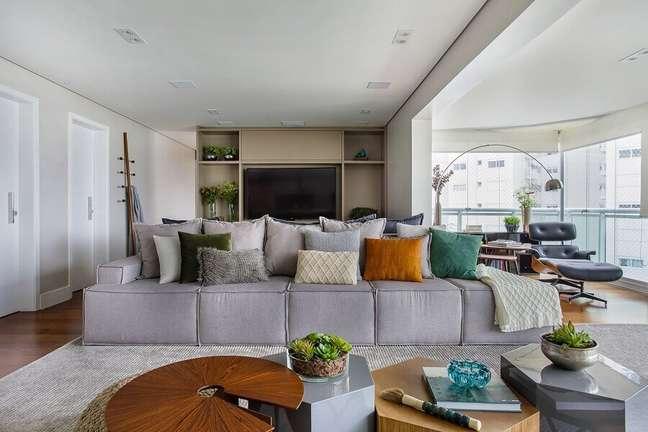 7. Decoração de sala grande com almofadas para sofá cinza sem braço – Foto: Tria Arquitetura