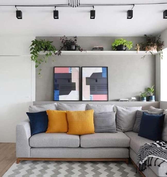 31. Decoração de sala moderna com trilho de luz e combinação de almofadas para sofá cinza de canto – Foto: Studio 92