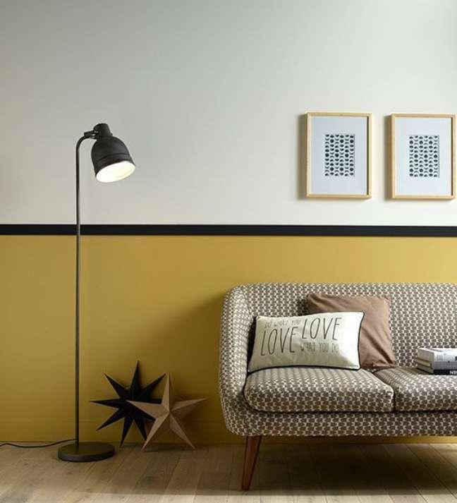 53. Sala de estar retrô com rodameio preto e parede mostarda – Foto Castorama via le cahier