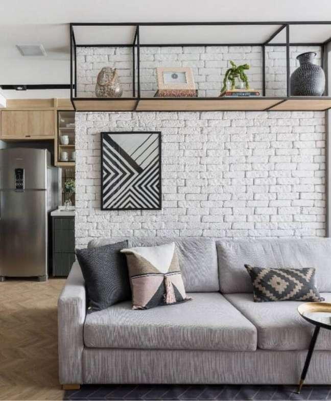 34. Decoração industrial para sala com parede tijolinho branco e almofadas para sofá cinza – Foto: Carol Miluzzi