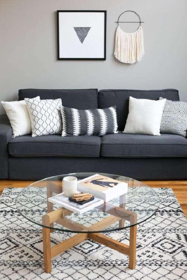 43. Mesa de centro redonda para sala simples decorada com almofadas para sofá cinza escuro – Foto: Apartment Therapy