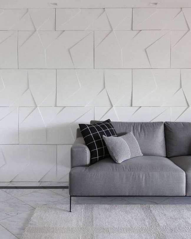 35. Decoração minimalista para sala com revestimento 3D e almofadas para sofá cinza – Foto: Bianchi & Lima