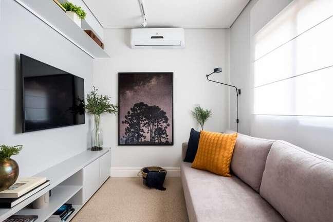 1. Cores para pintar sala pequena decorada com quadro de parede e almofadas coloridas – Foto: SP Estúdio