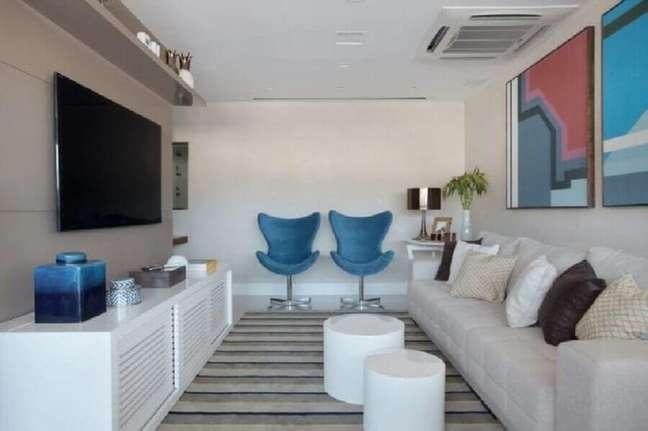 13. Cores para pintar sala pequena decorada com tapete listrado e quadros coloridos – Foto: Mariana Martini