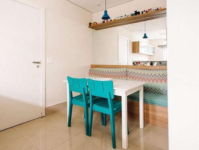 28. Cores para sala de jantar pequena e simples decorada com cadeira azul turquesa e parede espelhada – Foto: Codecorar
