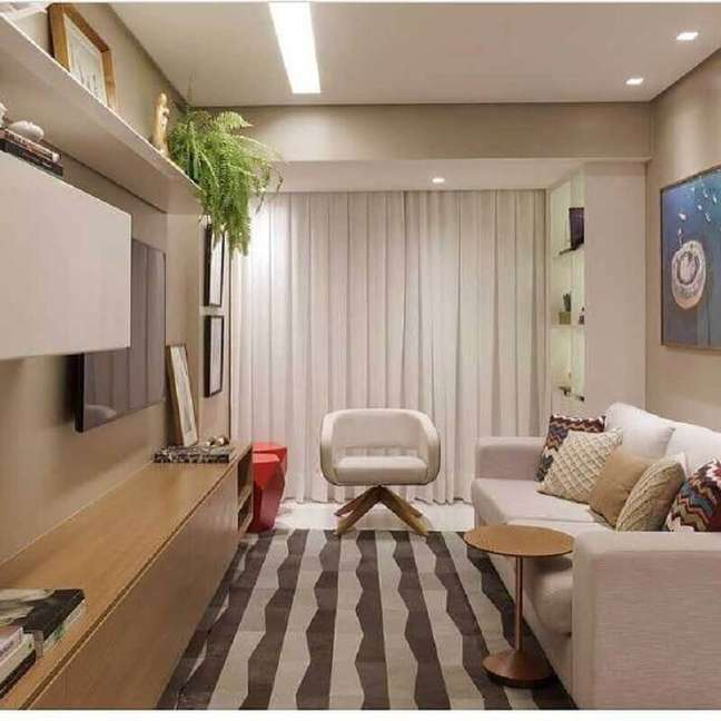 52. Cores para sala pequena decorada com rack de madeira e poltrona branca moderna – Foto: SD Arquitetura