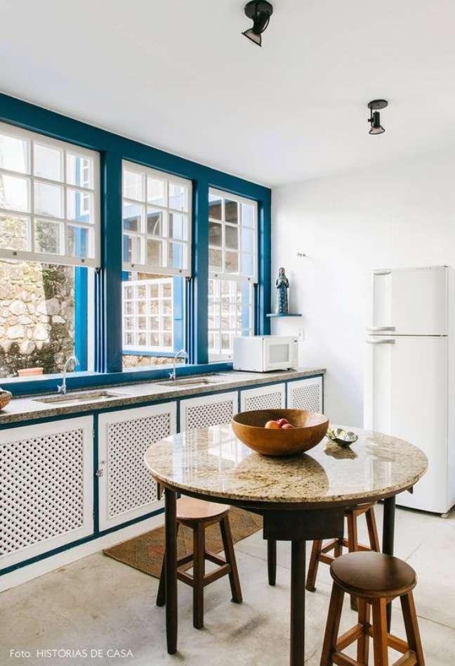 19. Porcelanato para cozinha moderna com msea de granito e banquetas de madeira – Foto Historias de Casa