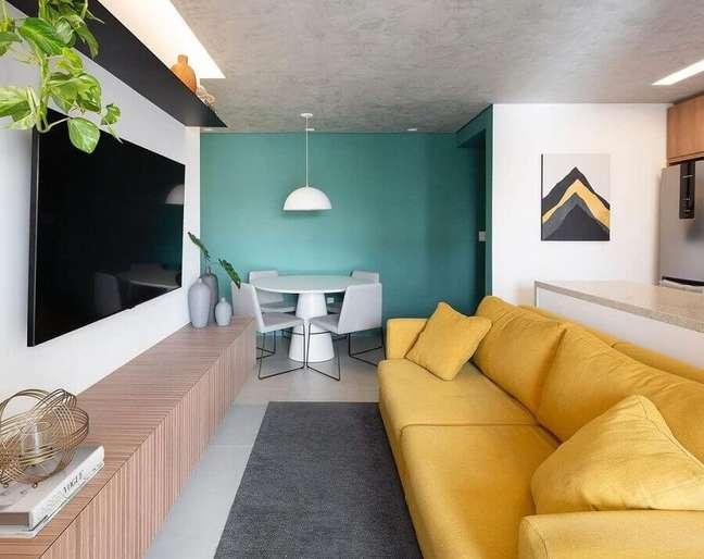 56. Ideia de cores para sala pequena e moderna decorada com sofá amarelo e parede azul – Foto: Fantato Nitoli