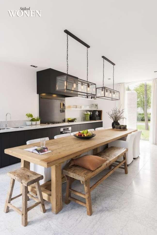 18. Porcelanato para cozinha moderna com mesa de madeira e armários pretos modernos – Foto Casa Claudia