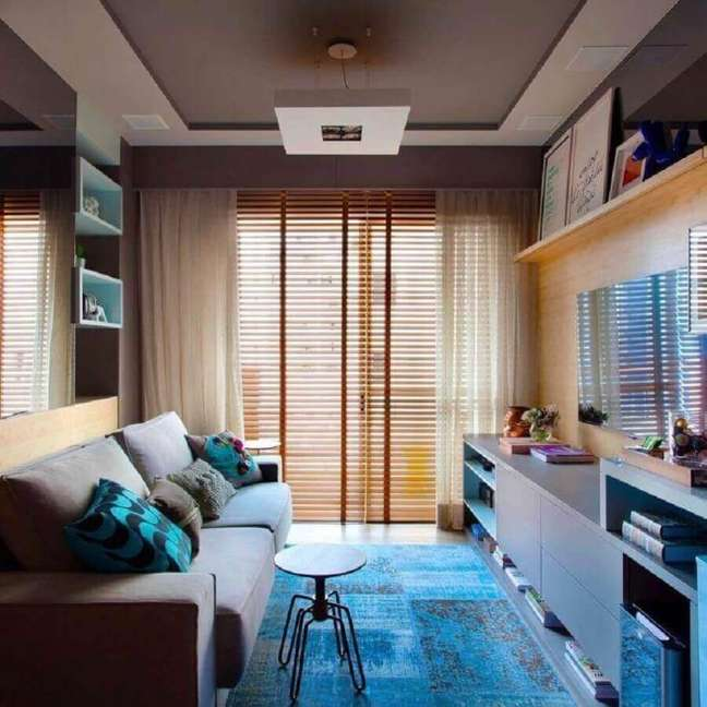 38. Cores para sala pequena decorada com tapete azul e persiana de madeira – Foto: Juliana Pippi