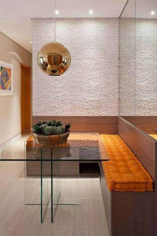 11. Cores para sala de jantar pequena decorada com mesa de vidro e canto alemão com almofadas laranja – Foto: Decor Fácil