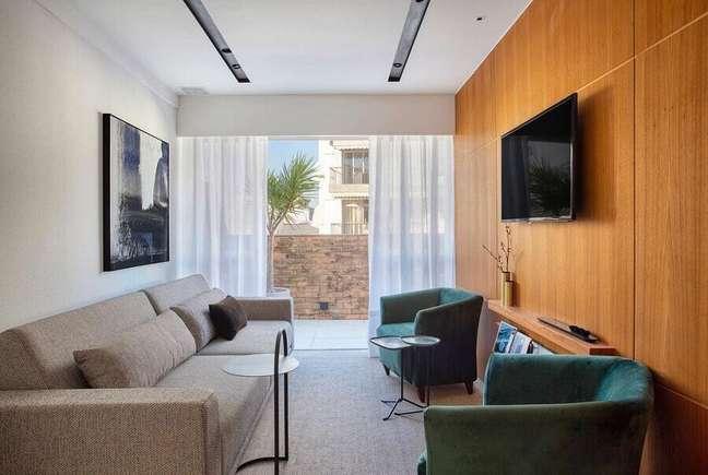3. Cores para sala pequena decorada com painel de madeira para TV – Foto: Hobjeto Arquitetura