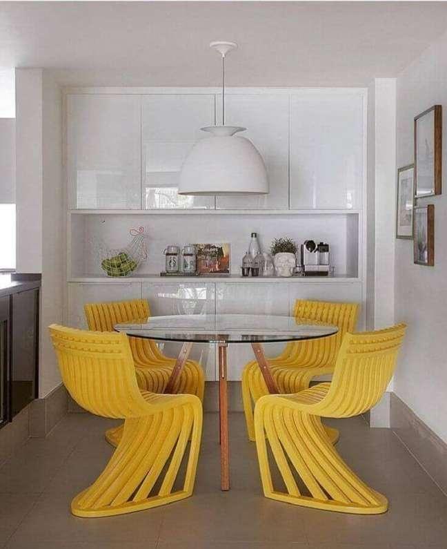 19. Cores para sala de jantar pequena decorada com cadeiras amarelas para mesa de vidro redonda – Foto: Yamagata Arquitetura