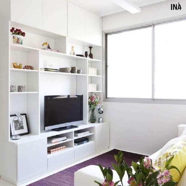 32. Cores para sala pequena decorada com estante de nichos branca – Foto: INÁ Arquitetura