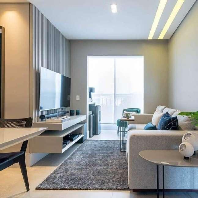 62. Paleta de cores para sala pequena decorada com tapete cinza e painel ripado – Foto: BF Arquitetas