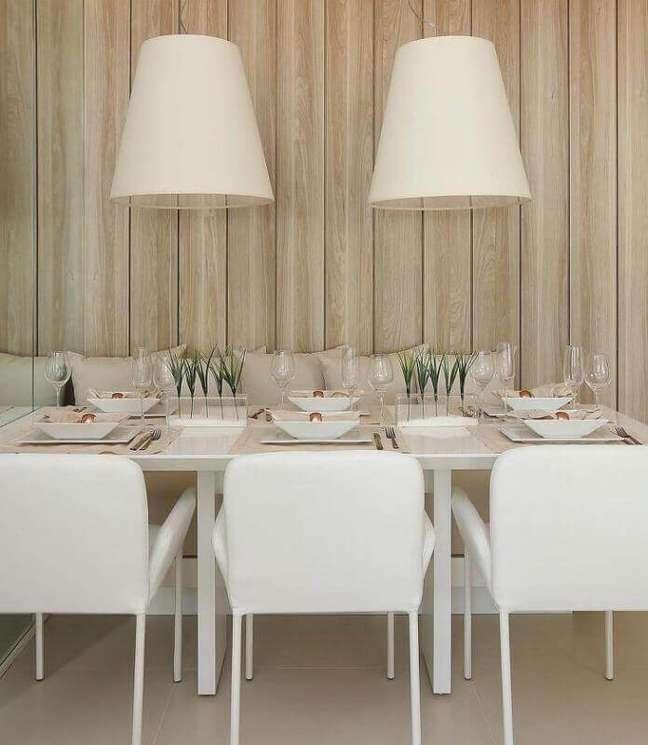 20. Cores para sala de jantar pequena decorada com luminária branca e revestimento de madeira para parede – Foto: Mariana Orsi