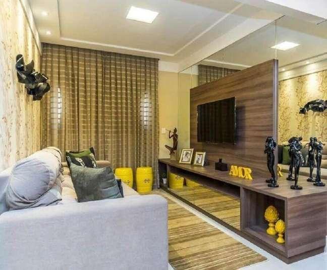10. Cores para sala pequena decorada com parede espelhada e rack de madeira com painel para TV – Foto: Renove Projetos