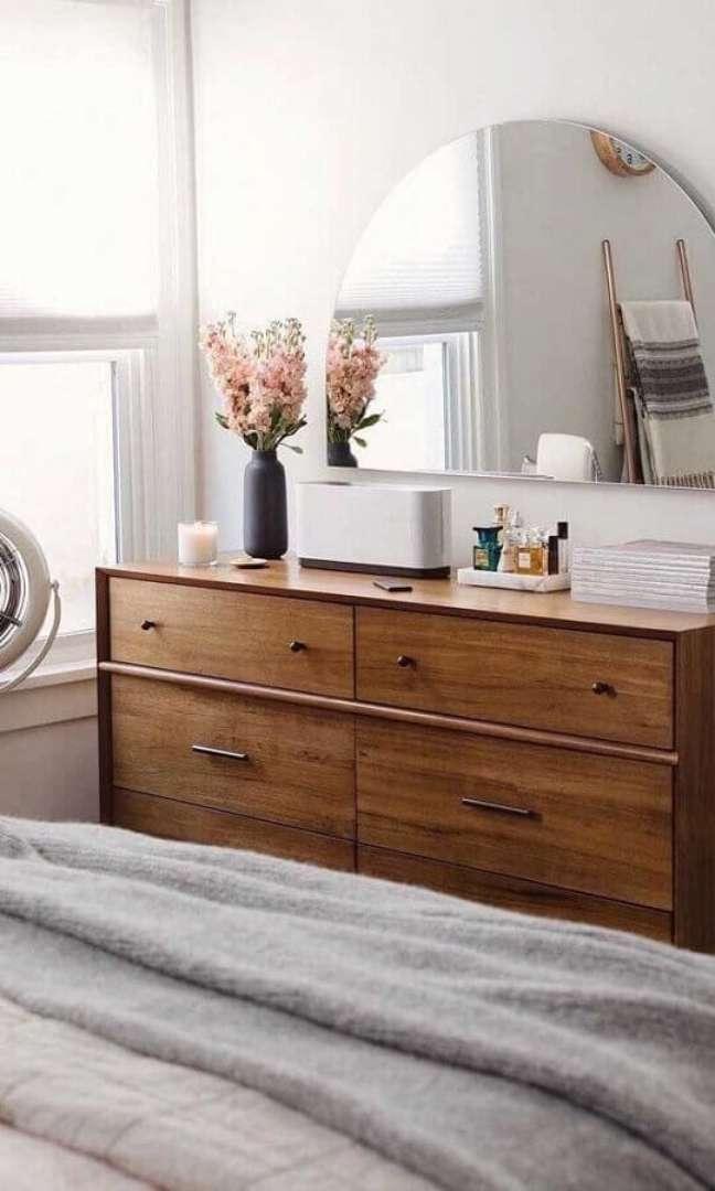 35. Cômoda de madeira para quarto decorada com espelho meia lua – Foto: Decor Fácil