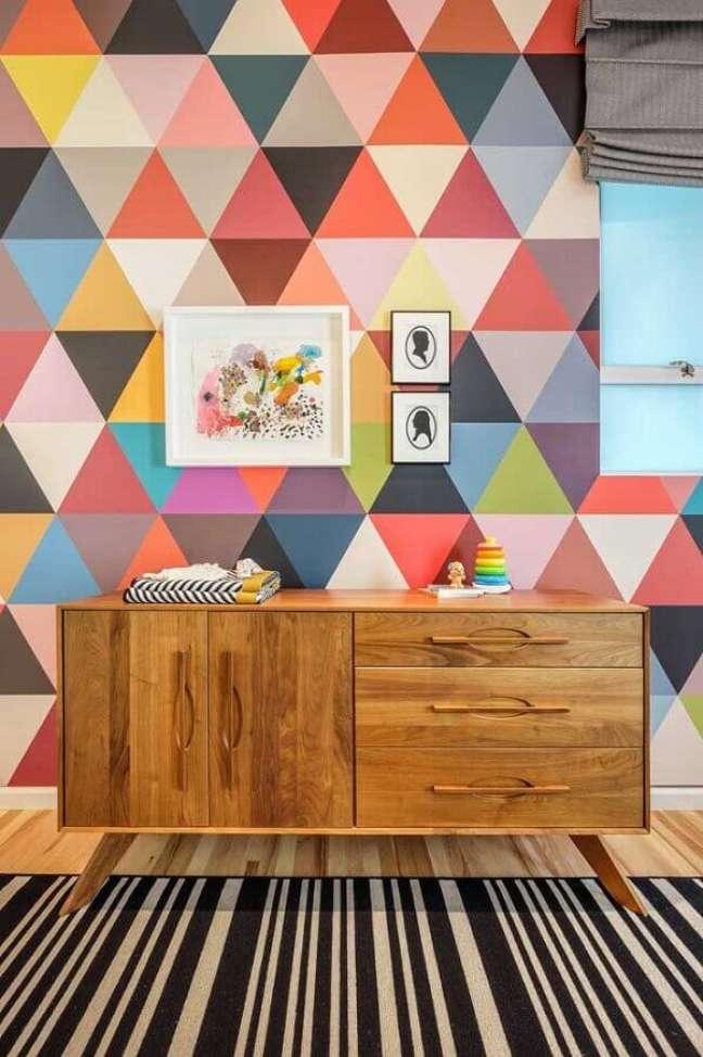 37. Cômoda de madeira para quarto decorado com papel de parede colorido e tapete listrado – Foto: Upper Terrace Nursery