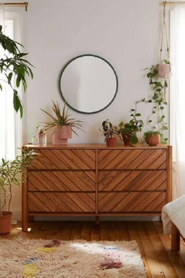 1. Cômoda de madeira para quarto decorado com vasos de plantas e espelho redondo – Foto: Urban Outfitters
