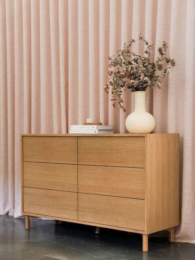 36. Cômoda de madeira para quarto decorado com cortina rosa – Foto: Unsplash
