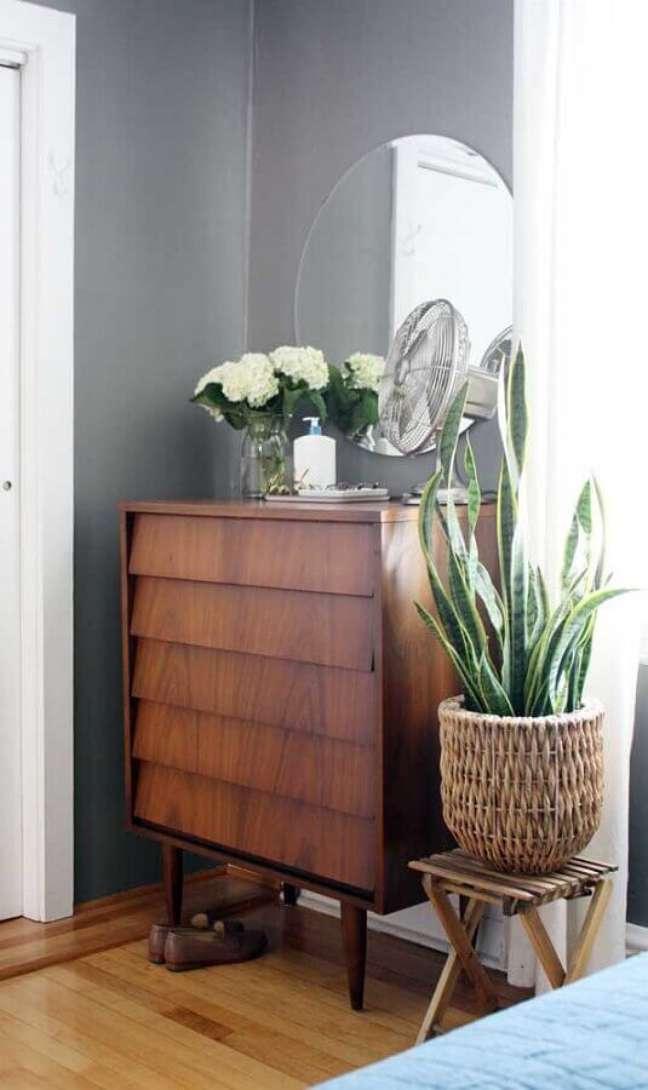 46. Decoração de quarto cinza com cômoda de madeira e espelho redondo sem moldura – Foto: Decor Fácil