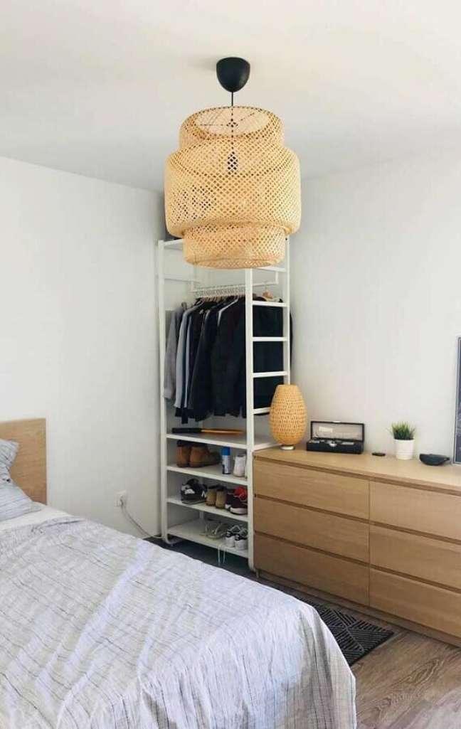 28. Cômoda de madeira para quarto branco decorado com pendente rústico e arara estilo industrial – Foto: Apartament Therapy