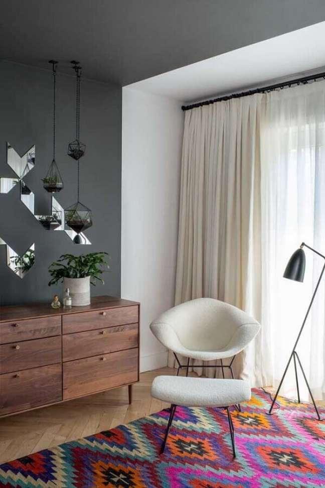 38. Cômoda de madeira para quarto decorado com tapete colorido e luminária de piso – Foto: Jessica Helgerson Interior Design