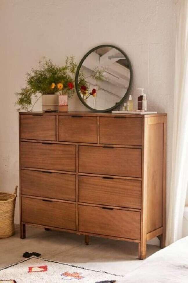26. Cômoda de madeira decorada com espelho redondo e vaso de flores – Foto: Urban Outfitters