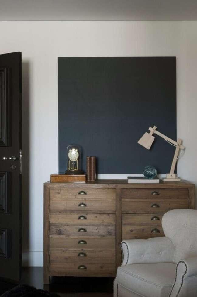 19. Cômoda antiga de madeira para decoração de quarto com poltrona cinza clara – Foto: Maurício Karam