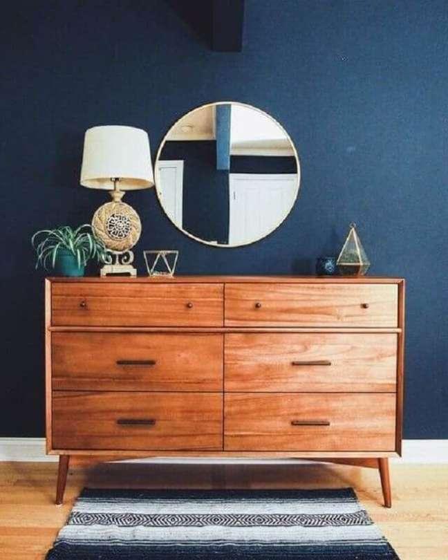 2. Cômoda de madeira para quarto azul decorado com espelho redondo – Foto: west elm