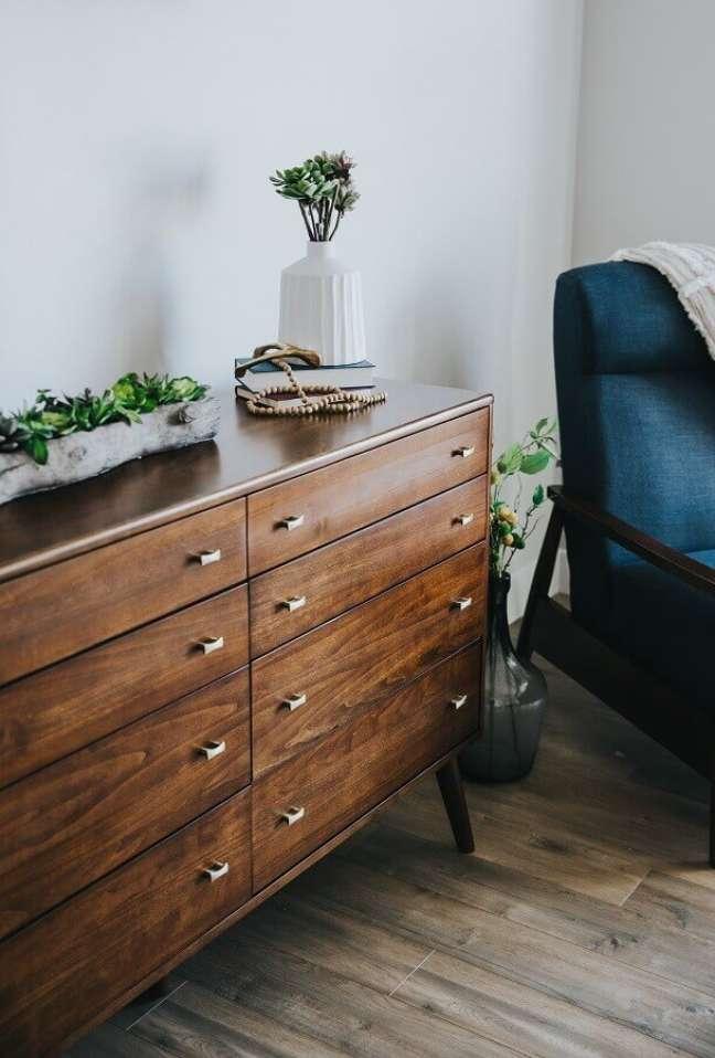 18. Cômoda antiga de madeira para decoração de quarto com poltrona azul marinho – Foto: Unsplash