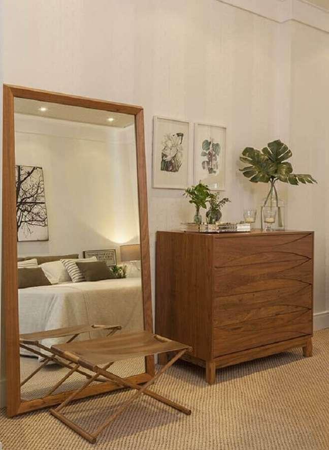 41. Cores neutras para quarto de casal decorado com cômoda de madeira e espelho de chão – Foto: Quartos Etc.