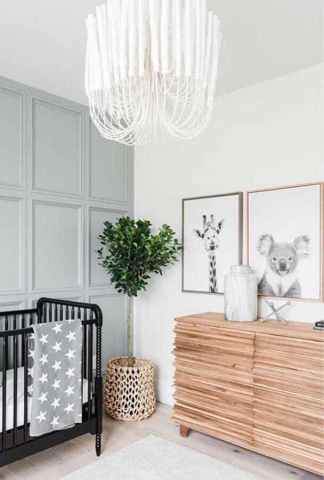 32. Cômoda de madeira para quarto de bebê decorado com berço preto e vaso de chão – Foto: No Decora
