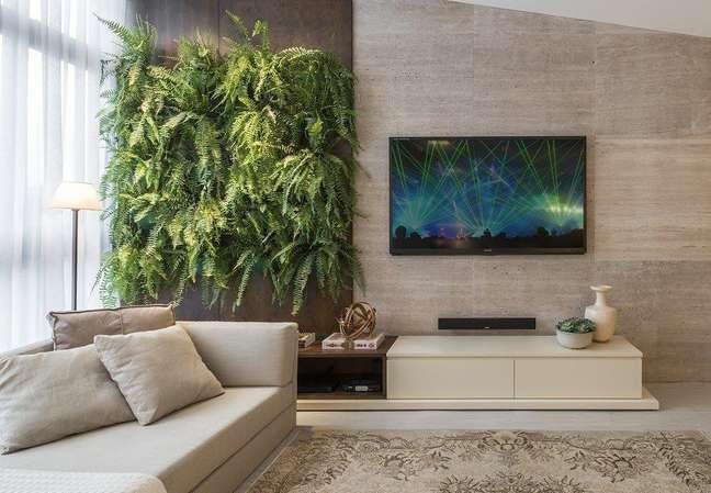 31. Sala de estar decorada com parede de samambaias e parede revestida com porcelanato Foto Estela Netto Arquitetura e Design