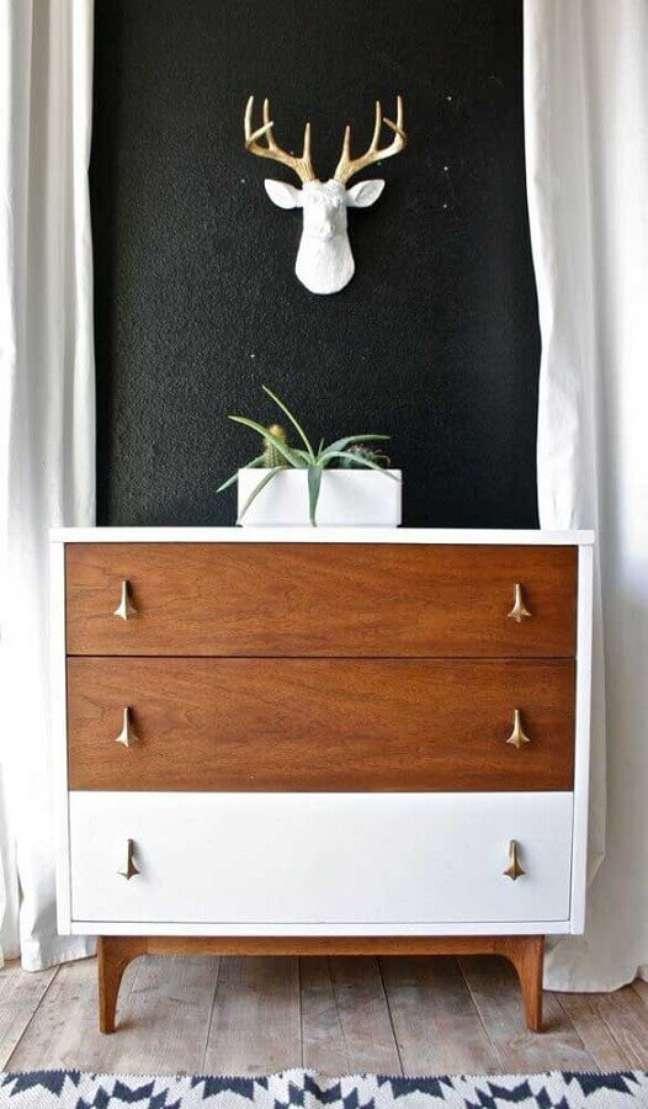 57. Modelo de cômoda de madeira diferente com puxadores dourado e gaveta branca – Foto: Elevated Serenity