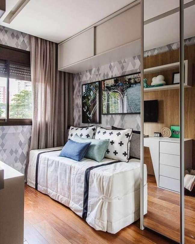 41. Papel de parede geométrico para decorado de quarto masculino solteiro pequeno com móveis planejados – Foto: Sesso e Dalanezi Arquitetura