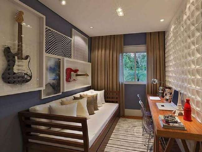 34. Escrivaninha de madeira para decoração de quarto masculino pequeno com guitarras na parede – Foto: Sesso & Dalanezi Arquitetura