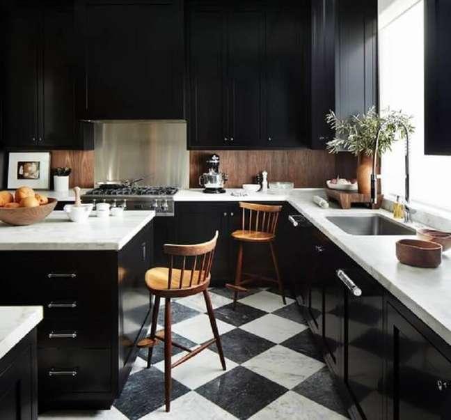 2. Decoração de cozinha preta com ilha e piso xadrez – Foto: Architectural Digest