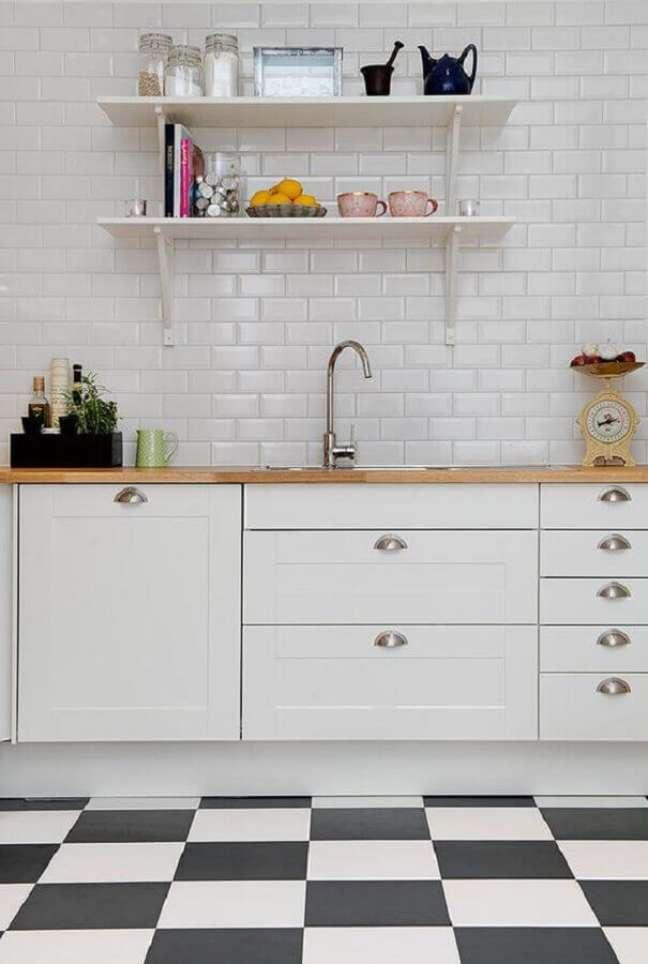 56. Piso xadrez preto e branco para decoração de cozinha planejada com bancada de madeira e metro white – Foto: Decor Fácil