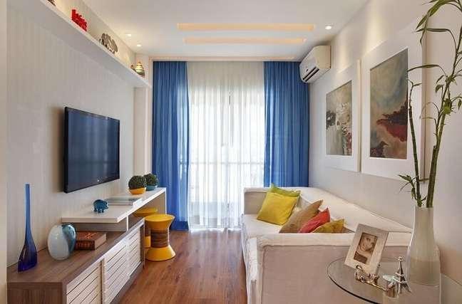 13. Tons de azul e amarelo invadem a decoração dessa sala planejada pequena. Projeto de Cyntia Sabat