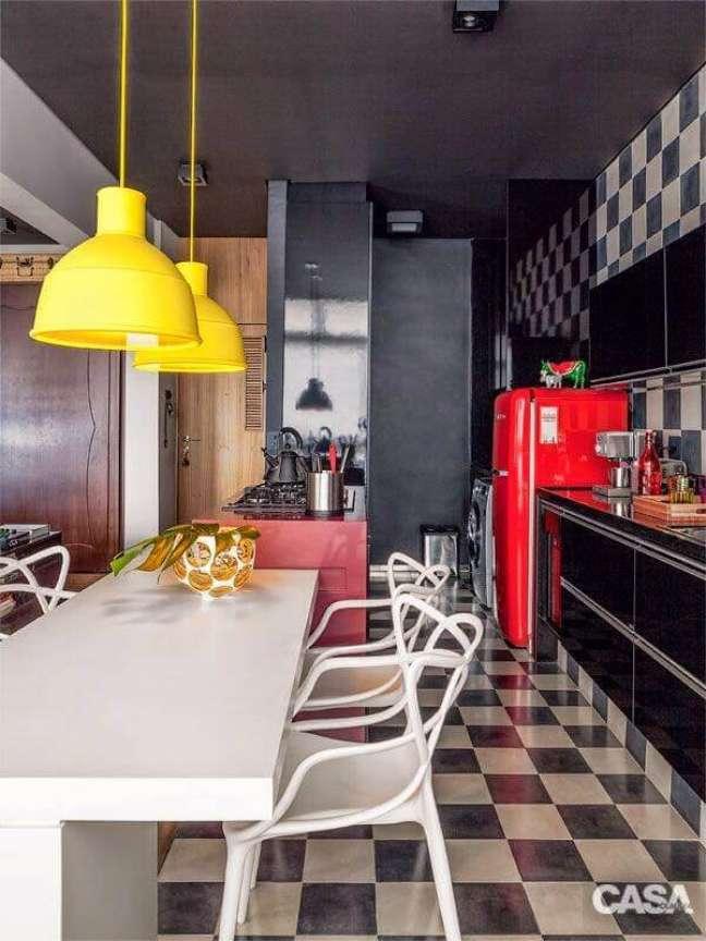 9. Piso xadrez para cozinha preta decorada com luminária amarela e geladeira vermelha – Foto: Casa Abril