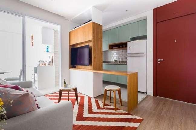 8. Sala pequena planejada com sofá cinza e tapete estampado vermelho. Projeto de Duda Senna