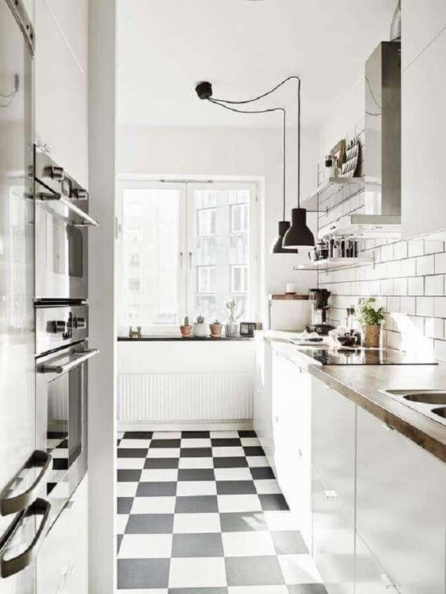 14. Cozinha branca decorada com bancada de madeira e piso xadrez preto e branco – Foto: My Ideal Home
