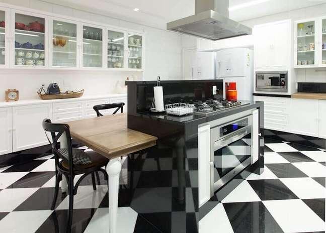 46. Piso xadrez para cozinha gourmet decorada com ilha vermelha e mesa de madeira – Foto: Gislene Lopes