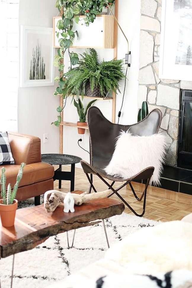 8. Sala decorada com poltrona butterfly marrom e almofada branca no ambiente boho – Foto Hello Liddy