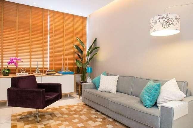 65. A persiana de madeira retém a entrada de luz natural na sala planejada pequena. Projeto de Marcelo Bastos