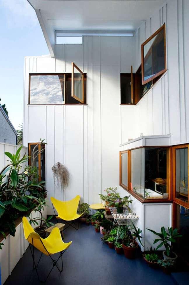 5. Área de lazer decorada com poltrona butterfly amarela e plantas – Foto David Boyle Architect